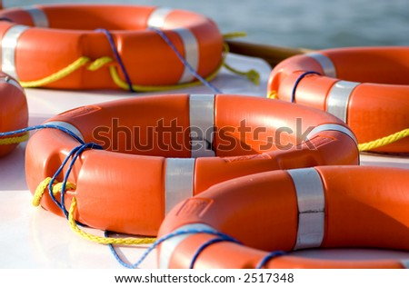 Bright orange life rings lay on top of a boat. safety, danger, rescue, security - stock photo