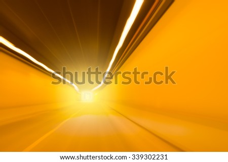 Bright orange light at the end of an undercover traffic tunnel or underpass with receding interior perspective