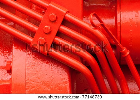 bright orange red oil dip stick and hydraulic lines on motor of agricultural equipment