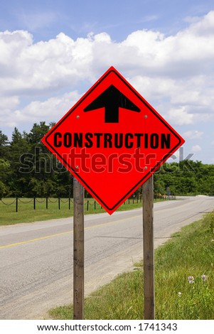 Bright Orange Reflective Construction Road Sign against a blue sky background on the side of a country rural road - stock photo