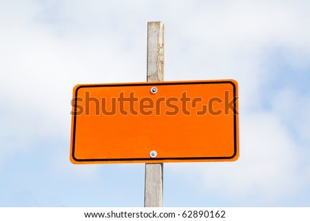 Bright orange road sign over cloudy sky