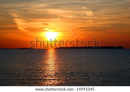 bright orange sunset over the calm waters of a  lake - stock photo