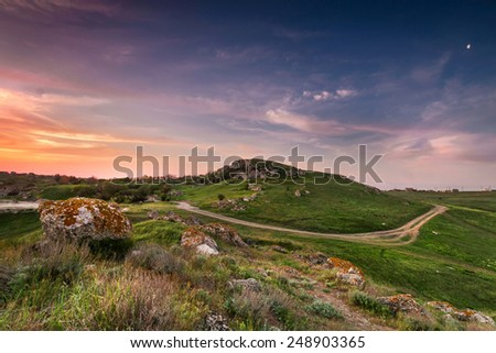 Bright orange sunset sky with red sunset over the green carpet of grass. The road skirts the hill and rushes into the distance - stock photo