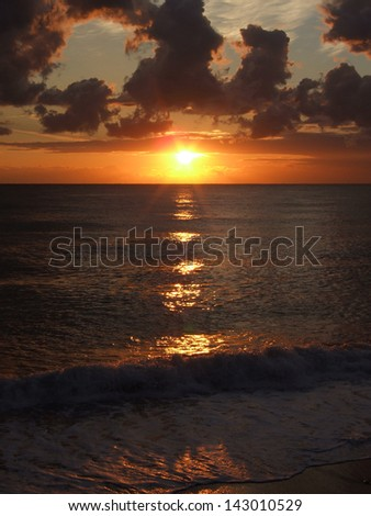 Bright orange sunset, surf and sun path