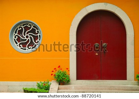 Bright orange wall facade with old door and a rounded window - stock photo