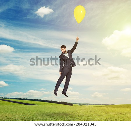 bright outdoors photo of flying man with yellow balloon - stock photo