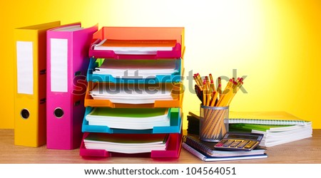 bright paper trays and stationery on wooden table on yellow background