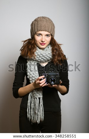 bright photographed a girl on a retro camera, dressed in winter clothing, Christmas and New Year concept, studio photo isolated on a gray background