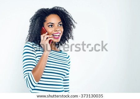 Bright picture of beautiful young mixed race woman with curly hair on white background. Girl smiling and using mobile phone - stock photo