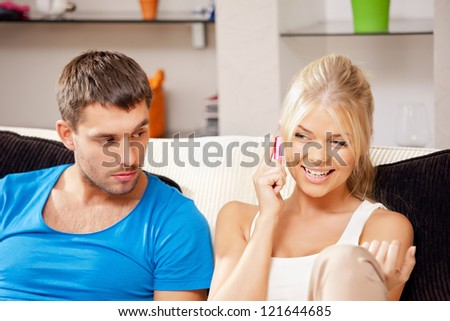 bright picture of couple with cellphone (focus on woman) - stock photo