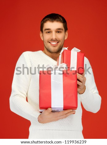 bright picture of handsome man holding many gift boxes. - stock photo