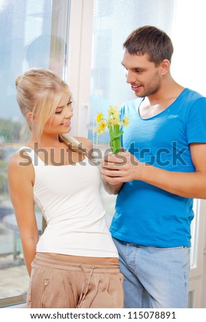 bright picture of happy romantic couple with flowers (focus on woman) - stock photo