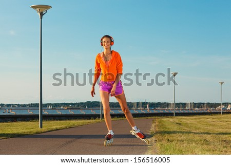 bright picture of happy young woman in headphones roller skating along the coast - stock photo