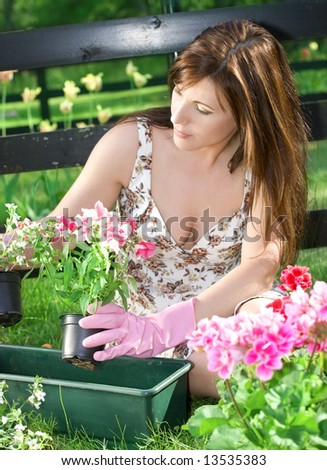 bright picture of lovely housewife potting plants - stock photo