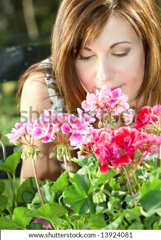 bright picture of lovely housewife potting plants (focus on nose and petals) - stock photo