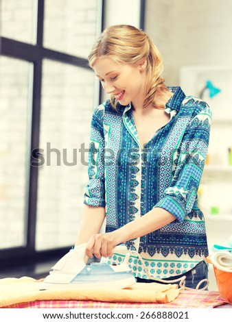 bright picture of lovely housewife with iron. - stock photo