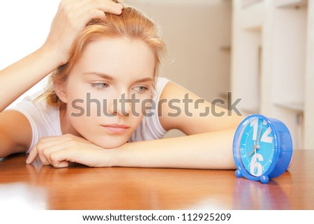 bright picture of pensive teenage girl with clock - stock photo