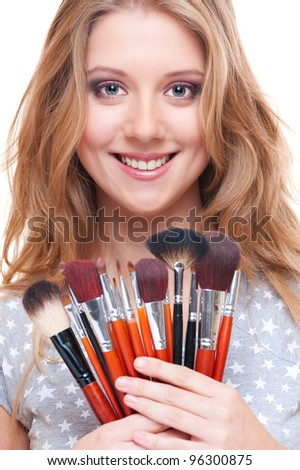 bright picture of smiley woman with make-up tools - stock photo