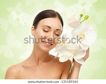 bright picture of smiling woman with white orchid flower