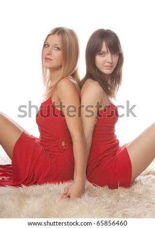 bright picture of two beautiful young girlfriends in red dress sitting