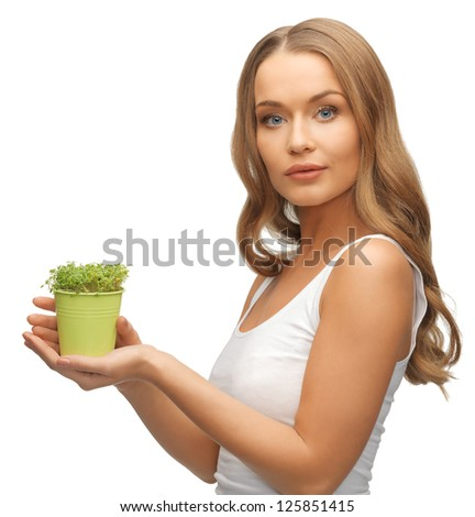 bright picture of woman with green grass in pot - stock photo