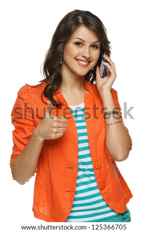 Bright picture of young woman talking on cellphone showing thumb up sign, over white background - stock photo
