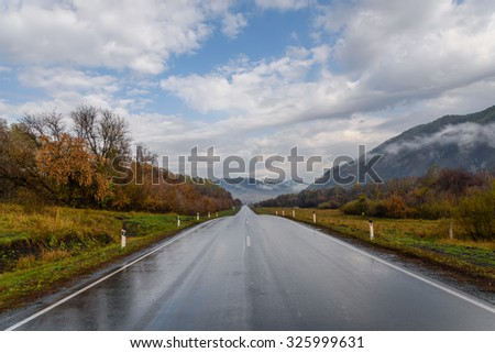 Bright picturesque view from the asphalt road, wet after the rain, mountains, fog, golden trees and grass against a blue sky with clouds - stock photo