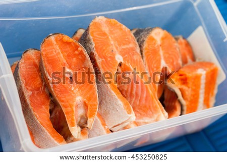 bright pieces of trout in the container for marinating - stock photo