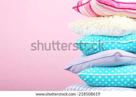 Bright pillows on pink background - stock photo