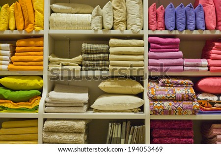 Bright pillows, towels, plaids, blankets and other home wear on shelves - stock photo