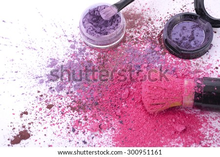 Bright pink and purple makeup powder scattered on white table with brush. - stock photo