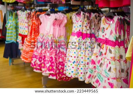 Bright pink kids dresses on stand in store - stock photo