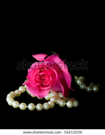 Bright pink rose and string of pearls on a black background