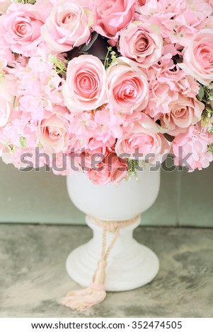 Bright pink roses in white roman vase,Vintage background.