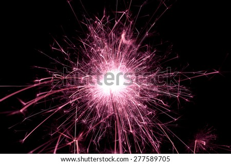 Bright pink sparks from a sparkler - stock photo