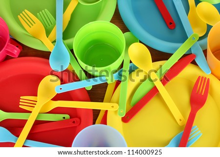 bright plastic disposable tableware on wooden background close-up - stock photo