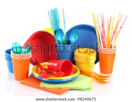 Bright plastic tableware and napkins isolated on white - stock photo