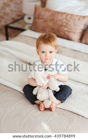 bright portrait of adorable baby with toy hare in her hands sitting on the bed  - stock photo