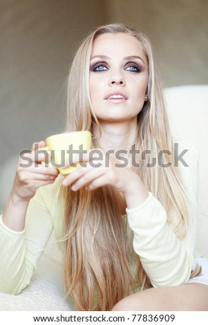 Bright portrait of beautiful woman with cup of tea sitting on the sofa - stock photo