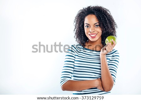 Bright portrait of beautiful young mixed race woman with curly hair on white background. Girl looking at camera, smiling and holding green apple - stock photo