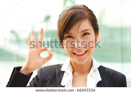 "Bright portrait of business lady showing ""OK"" sign"