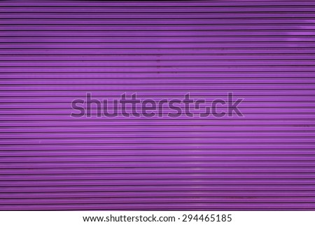 Bright purple metal sliding door with key hole, taken on a cloudy day. - stock photo