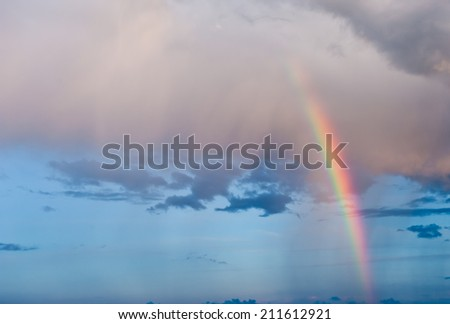 Bright rainbow in the sky with clouds on sunset