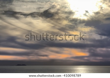 Bright rays of sun breaks through clouds over ocean expanse. Pacific ocean in fall