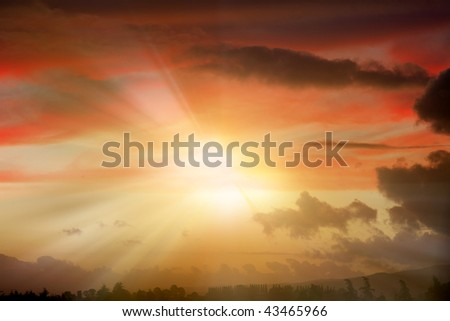 Bright rays of sunlight beam out in dramatic sky. - stock photo