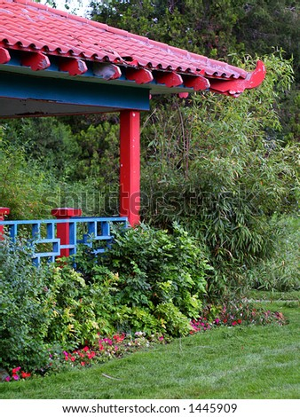 Bright red and cyan Chinese pagoda-style gazebo amidst green plants and trees.