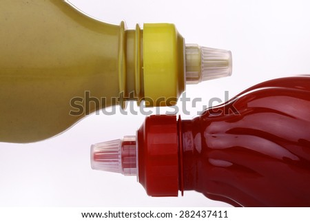 Bright red and dark yellow bottles of ketchup and mustard on a white background closeup, horizontal photo - stock photo