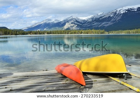 Bright Red and Yellow Canoes on the Shore of Clear, Still Lake in the Rocky Mountains - stock photo