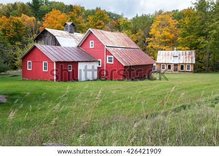 Bright Red barns at Bufka Farm at Sleeping Bear Dunes National Lakeshore surrounded by an autumn background. - stock photo