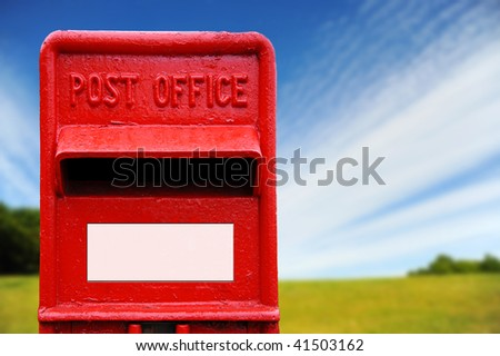 Bright red British post box with countryside background